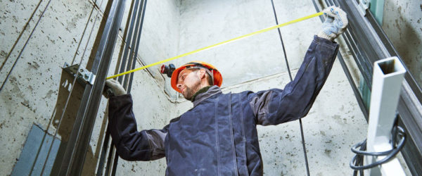 machinist worker measure and adjusting elevator construction with in lift shaft